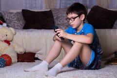 kinderen, technologie, Internet-mededeling en mensenconcept - jongen met smartphone texting bericht of speelspel thuis royalty-vrije stock afbeelding