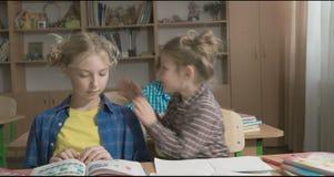 Kinderen of twee gelukkige meisjes die en thuiswerk in schoolklaslokaal leren doen stock videobeelden