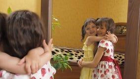 Kinderen voor de spiegel De zusters koesteren Meisjes voor een spiegel stock videobeelden