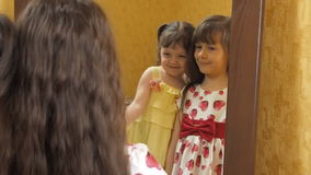 Kinderen voor de spiegel De zusters koesteren Meisjes voor een spiegel stock video