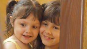 Kinderen voor de spiegel De zusters koesteren Stof op de spiegel Meisjes voor een spiegel stock videobeelden