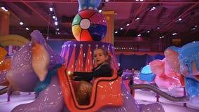 Kinderenaantrekkelijkheid Meisje die op een kindolifant vrolijk-gaan-rond berijden in spelpark in het wandelgalerijcentrum stock footage