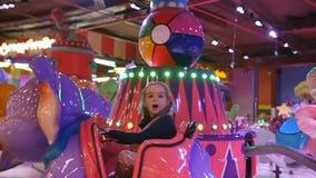 Kinderenaantrekkelijkheid Meisje die op een kindolifant vrolijk-gaan-rond berijden in spelpark in het wandelgalerijcentrum stock videobeelden