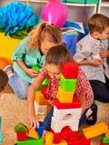 Kinderenbouwstenen in kleuterschool Groepsjonge geitjes die stuk speelgoed vloer spelen Stock Foto's