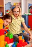 Kinderenbouwstenen in kleuterschool Groepsjonge geitjes die stuk speelgoed vloer spelen Royalty-vrije Stock Afbeeldingen