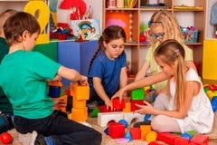 Kinderenbouwstenen in kleuterschool Groepsjonge geitjes die stuk speelgoed vloer spelen Royalty-vrije Stock Foto's