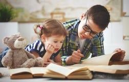 Kinderenbroer en zuster, jongen en meisje die een boek lezen Stock Fotografie