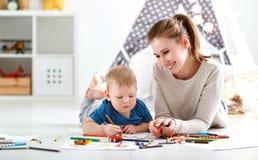 Kinderencreativiteit moeder en babyzoon die zich samentrekken stock fotografie