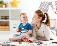 Kinderencreativiteit moeder en babyzoon die zich samentrekken stock afbeeldingen