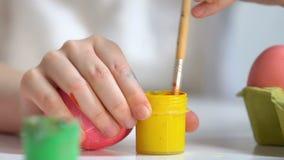 Kinderenhanden die gele verf voorbereiden om patroon op ei, Pasen-voorbereiding te trekken stock footage