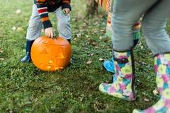 Kinderenhanden en benen die deksel op Halloween-pompoen zetten Stock Afbeeldingen