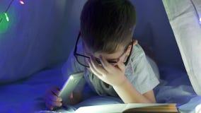Kinderenhobby, mooi jong geitje in glazen die boek thuis lezen in dark met flitslicht onder deken stock videobeelden