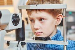 Kinderenoftalmologie Jongen in optometristonderzoek stock afbeelding