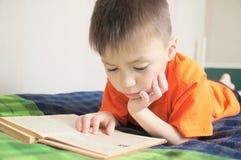 Kinderenonderwijs, het boek die van de jongenslezing op bed, kindportret liggen die met boek, onderwijs, interessant verhalenboek Royalty-vrije Stock Foto's