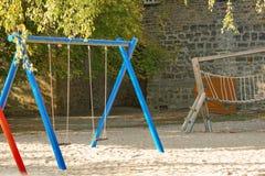 Kinderenspeelplaats op werfactiviteiten in openbaar die park door groene bomen bij zonlichtochtend wordt omringd stock fotografie