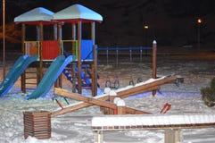 Kinderenspeelplaats in sneeuw wordt behandeld die stock foto