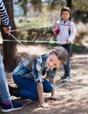 Kinderenspelen Het meisje gaat door de verwarde kabel Stock Foto's