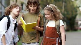 Kinderentieners die enthousiast het boek op de manier lezen aan school Terug naar School Gelukkige kinderjaren stock footage