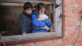 Kinderenvluchtelingen tegen de achtergrond van gebombardeerde huizen Oorlog stock video