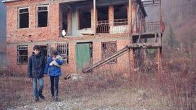 Kinderenvluchtelingen tegen de achtergrond van gebombardeerde huizen Oorlog stock footage
