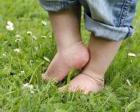 Kinderfüße auf Gras Stockfoto