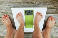 Kinderfüße, die auf digitaler Gewichtsskala vor seiner Mutter, Diätempfehlung stehen lizenzfreies stockfoto
