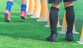 Kinderfüße mit den Stiefeln, die auf Ausbildungskegel auf Fußballboden ausbilden stockbilder