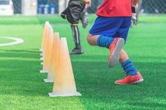 Kinderfüße mit den Stiefeln, die auf Ausbildungskegel auf Fußballboden ausbilden lizenzfreie stockfotografie