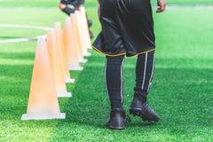 Kinderfüße mit Fußballtraining auf Ausbildungskegel auf Fußballboden stockfoto