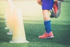 Kinderfüße mit Fußballtraining auf Ausbildungskegel auf Fußballboden lizenzfreies stockbild