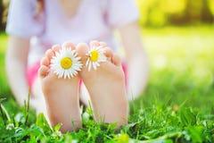 Kinderfüße mit Gänseblümchen blühen auf grünem Gras in einem Sommerpark Lizenzfreie Stockfotos