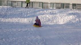 Kinderfahrt auf eine Platte auf Hügel, Kind, das im Winter rodelt stock video