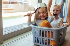 Kinderfahrten in einem Wäschekorb lizenzfreie stockbilder