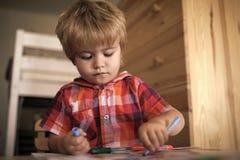 Kinderfarben mit Filzstiften Kind oder blonde glückliche Jungenfarbe mit Filzstift Lizenzfreie Stockfotografie