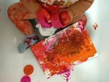 Kinderfarben mit mit den Fingern Stockfotografie