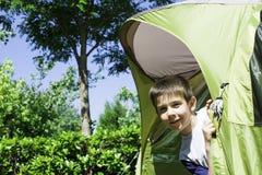 Kinderflüchtige blicke von einem Zelt Stockbild