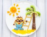 Kinderfrühstück mit Pfannkuchen und Früchten Karikaturheld Stockfotos