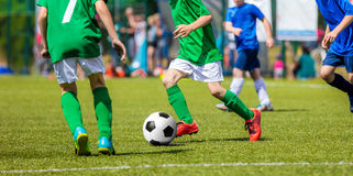 Kinderfußball-Spieler, die mit dem Ball laufen Kinder im Blau und Stockbilder