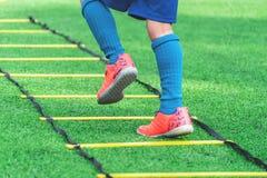 Kinderfußballstiefel, die auf Beweglichkeitsgeschwindigkeitsleiter im Fußballtraining ausbilden stockfoto