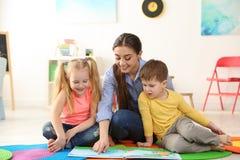 Kindergärtnerin-Lesebuch zu den Kindern Lernen und Spielen stockfotografie