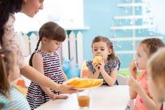 Kindergärtnerin und Vorschülerkinder, die Bruch für Obst und Gemüse haben lizenzfreies stockbild
