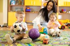 Kinderg?rtnerin, die um Kinder im Kindertagesst?tte sich k?mmert Kleinkindkleinkinder spielen zusammen mit Entwicklungsspielwaren stockfoto