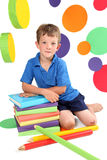 Kindergarten. Beautiful boy sitting next to textbooks and uge pencils with bright circles in the background royalty free stock photo