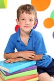 Kindergarten. Beautiful boy sitting next to textbooks and uge pencils with bright circles in the background royalty free stock images