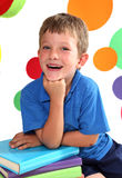 Kindergarten. Beautiful, laughing boy leaning on his hand with bright circles in the background royalty free stock photos