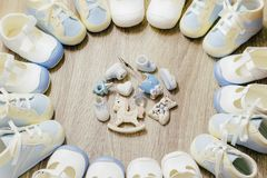 Kindergarten. Baby boy blue bootees circle frame on a wooden background with toys accessories in the middle. Top view