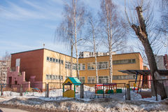 Kindergarten building and a playground behind the fence royalty free stock photos