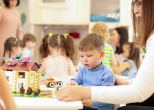 Kindergarten child boy building toy house in playroom at preschool, education concept. royalty free stock photography