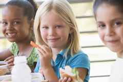 Kindergarten children eating lunch stock photo