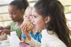 Kindergarten children eating lunch stock image